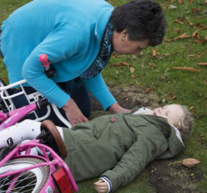 Woman attending to injured small child lying on the ground